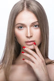 Beautiful young girl with a light natural make-up and red nails. Stock Photo
