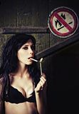 Beautiful girl lights cigarette near No fire sign  Stock Images