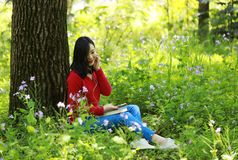 Beautiful young girl Listen to music on a mobile phone while sitting under giant oak Royalty Free Stock Photography