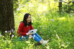 Beautiful young girl Listen to music on a mobile phone while sitting under giant oak Stock Photos