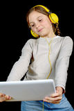 A beautiful young girl listening to music with a digital tablet Stock Images