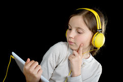 A beautiful young girl listening to music with a digital tablet Stock Photo