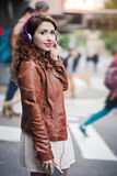 Beautiful young girl listening to music with headphones in the city. Beautiful young girl in th dress listening to music with headphones in the city Royalty Free Stock Images