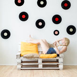Beautiful young girl listening to music at home sitting on the c Stock Photos
