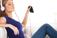 Beautiful young girl listens to music on headphones. Royalty Free Stock Photos