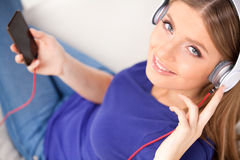 Beautiful young girl listens to music on headphones Stock Image