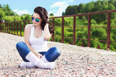 Beautiful young girl with long black hair in a Sunny summer day sitting on the bridge in sunglasses Royalty Free Stock Photos