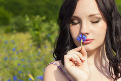Beautiful young girl with long black hair with a wreath of cornflowers with makeup walking in the Sunny summer day in the field wi Stock Photos