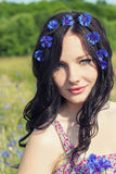 Beautiful young girl with long black hair with a wreath of cornflowers with makeup walking in the Sunny summer day in the field wi Royalty Free Stock Photography