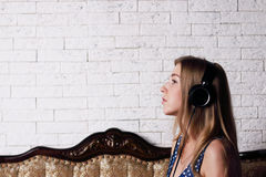Beautiful young girl with long blond hair sitting on couch. With headphones stock image