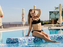 Cute, pretty and sexy young woman in a black, beautiful swimsuit on a pool background. Stock Photos