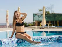 Cute, pretty and sexy young woman in a black, beautiful swimsuit on a pool background. Stock Photography