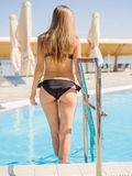 Cute, pretty and sexy young woman in a black, beautiful swimsuit on a pool background. Royalty Free Stock Photography