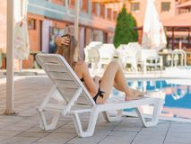 Cute, pretty and young woman in a black, beautiful swimsuit on a pool background. Stock Images