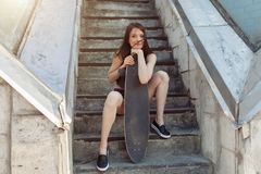 Beautiful young girl with a long board in the city. The concept of modern youth. Active fun holiday. Beautiful young girl with a long board in the city. The stock photography