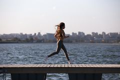 Beautiful young girl with long brown hair dressed in a sport uniform is running on the wooden pier on the summer day . stock photo