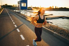 Beautiful young girl with long brown hair dressed in sports clothes runs on the road along the water on the sunset royalty free stock photography