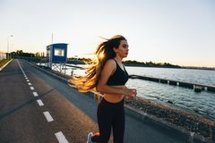 Beautiful young girl with long brown hair dressed in sports clothes runs on the road along the water on the sunset stock photos