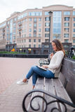 A beautiful young girl with long brown hair sitting on the bench with book and biting glasses while reading. She left the house on royalty free stock images