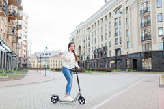 Beautiful young girl with long brown hair stopped while riding the scooter to talk to a friend on the phone on the background of t. He new residential quarter Royalty Free Stock Photography