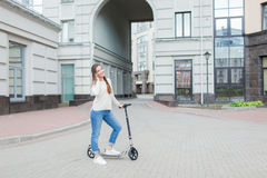 Beautiful young girl with long brown hair stopped while riding the scooter to talk to a friend on the phone on the background of t. He new residential quarter Stock Image
