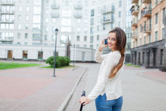 Beautiful young girl with long brown hair stopped while riding the scooter to talk to a friend on the phone on the background of t. He new residential quarter Stock Images