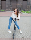 Beautiful young girl with long brown hair stopped while riding the scooter to talk to a friend on the phone on the background of t. He new residential quarter Royalty Free Stock Photos