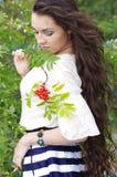 Beautiful young girl with long dark hair with rowan Stock Photos