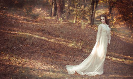 Beautiful young girl in a long gentle waving bright dress stands in the autumn forest. Bride on a walk. stock photography