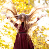 Beautiful young girl with long hair flying in the autumn park day Royalty Free Stock Photos