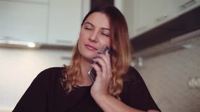 Beautiful young girl makes a call to her girlfriend using a smartphone and smiles. Home style. Beautiful young girl with long hair is making a call to her friend stock video footage
