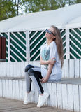 The Beautiful Young Girl with Long Hair in Sunglasses sits at white wooden Steps. Stock Image