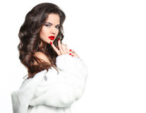 Beautiful young girl with long hairstyle curly hair and red lips. Makeup, fashion woman in fur coat isolated on white background stock image