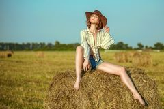 Beautiful young girl with long thin legs and naked belly in a cowboy hat and denim shorts on the yellow field poses stock photography