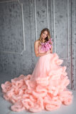Beautiful young girl with long wavy hair holding a bouquet of flowers in pink dress-the cloud is in interior Royalty Free Stock Photo