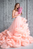 Beautiful young girl with long wavy hair holding a bouquet of flowers in pink dress-the cloud is in interior Stock Image