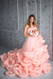 Beautiful young girl with long wavy hair holding a bouquet of flowers in pink dress-the cloud is in interior Royalty Free Stock Photography
