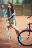 Beautiful young girl with longboard and bicycle standing  Stock Photos