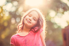 Beautiful young girl looking at camera and smiling on sunny day. Lovely young girl looking at camera smiling on a sunny day with beautiful bokeh background Stock Photo