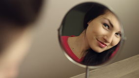 Beautiful young girl looking In The Mirror stock video