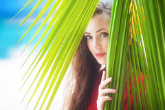 A beautiful young girl looking through palm leaves, tropical vac Stock Photos