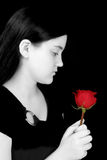 Beautiful Young Girl Looking At Red Rose Against Black. Beautiful young girl with long black hair and pale complexion in black and white looking at red rose Stock Image