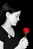 Beautiful Young Girl Looking At Red Rose Against Black. Beautiful young girl with long black hair and pale complexion in black and white looking at red rose Royalty Free Stock Photography