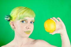 Beautiful young girl looks at lemon on green background Royalty Free Stock Images