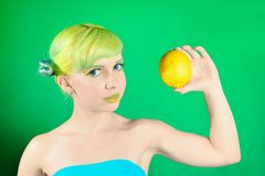 Beautiful young girl looks at lemon on green background Royalty Free Stock Photo