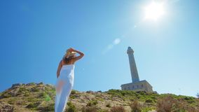 A beautiful young girl, looks at an lighthouse, in a straw hat. Concept: recreation, beautiful view, freedom, travel and. Breathe stock video footage