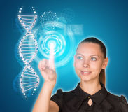 Beautiful young girl looks at model of DNA and Royalty Free Stock Photography