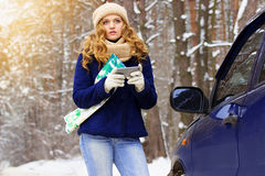 Beautiful young girl lost on the forest road, holding map and phone navigator, standing near car on the road, wearing blue jacket. Stock Image