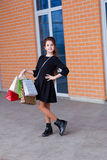 Beautiful young girl with a lot of packages at the outlet of the Stock Photos