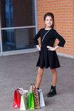Beautiful young girl with a lot of packages at the outlet of the Royalty Free Stock Image